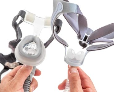 A sleep test clinician holds two different types of CPAP masks.