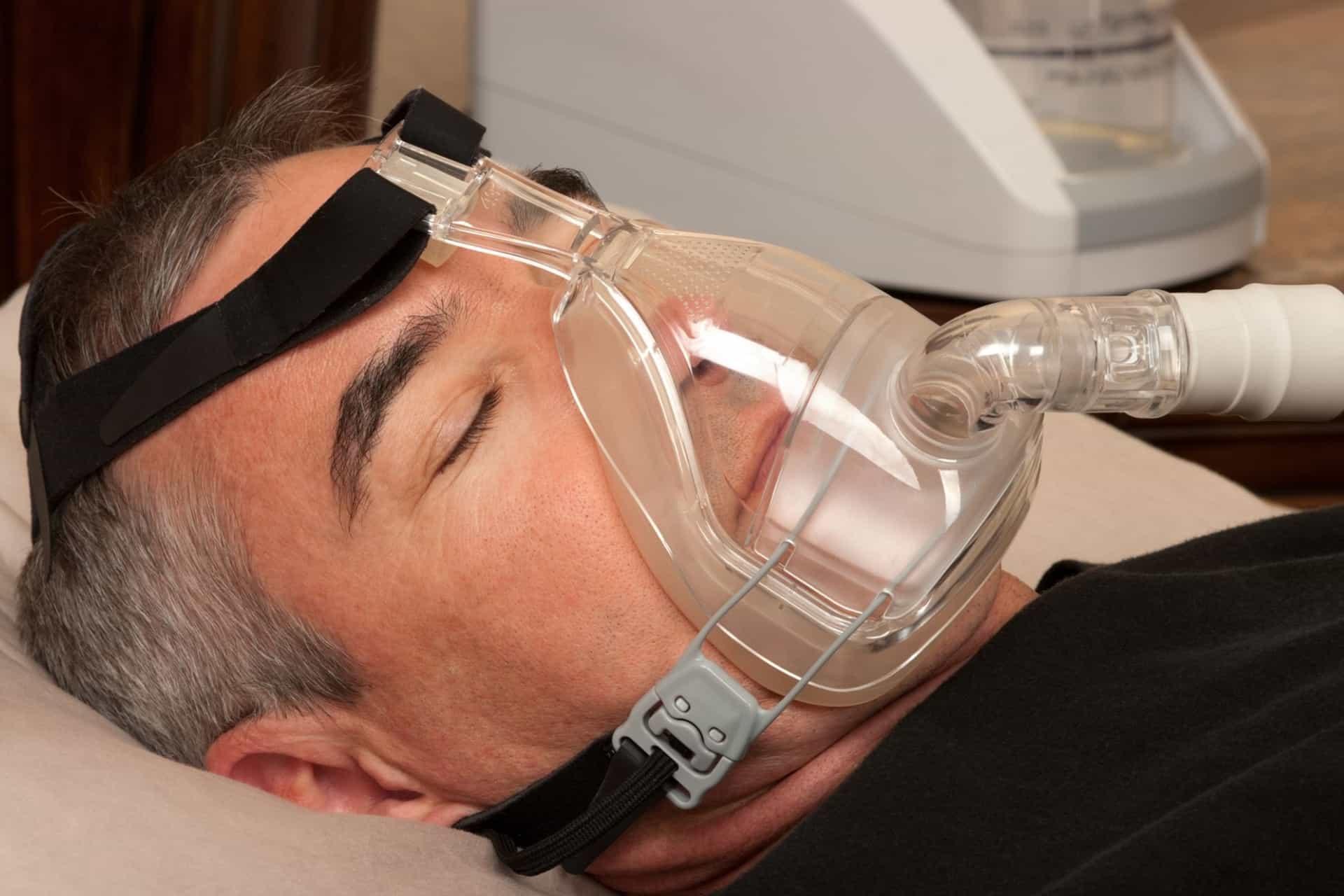 Man sleeping with a CPAP device to treat sleep apnea.