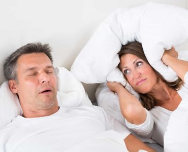A woman covers her ears with a pillow because the man is snoring due to sleep apnea.