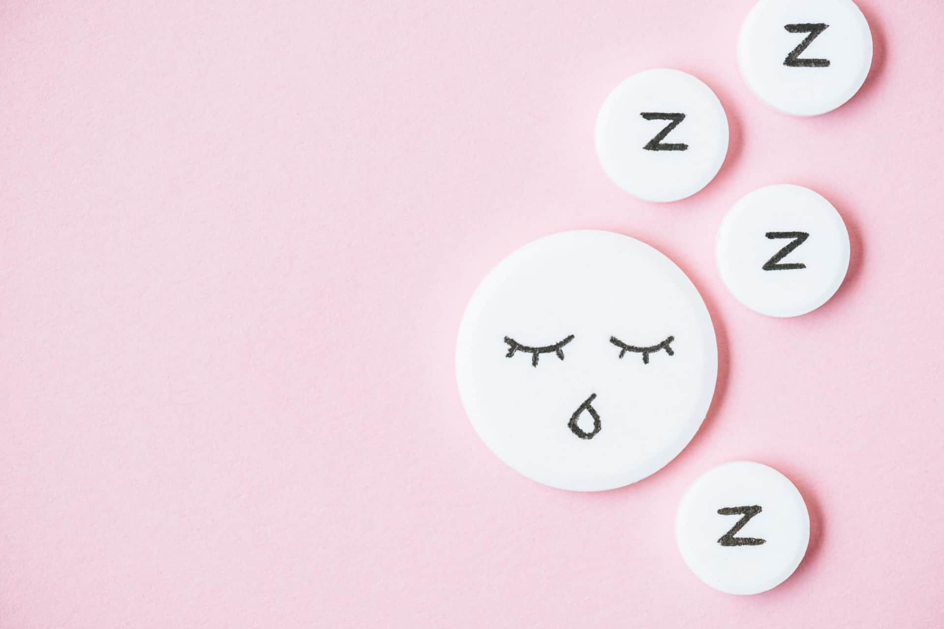 Sleeping pills with Zzzs written on them are shown against a pink background.