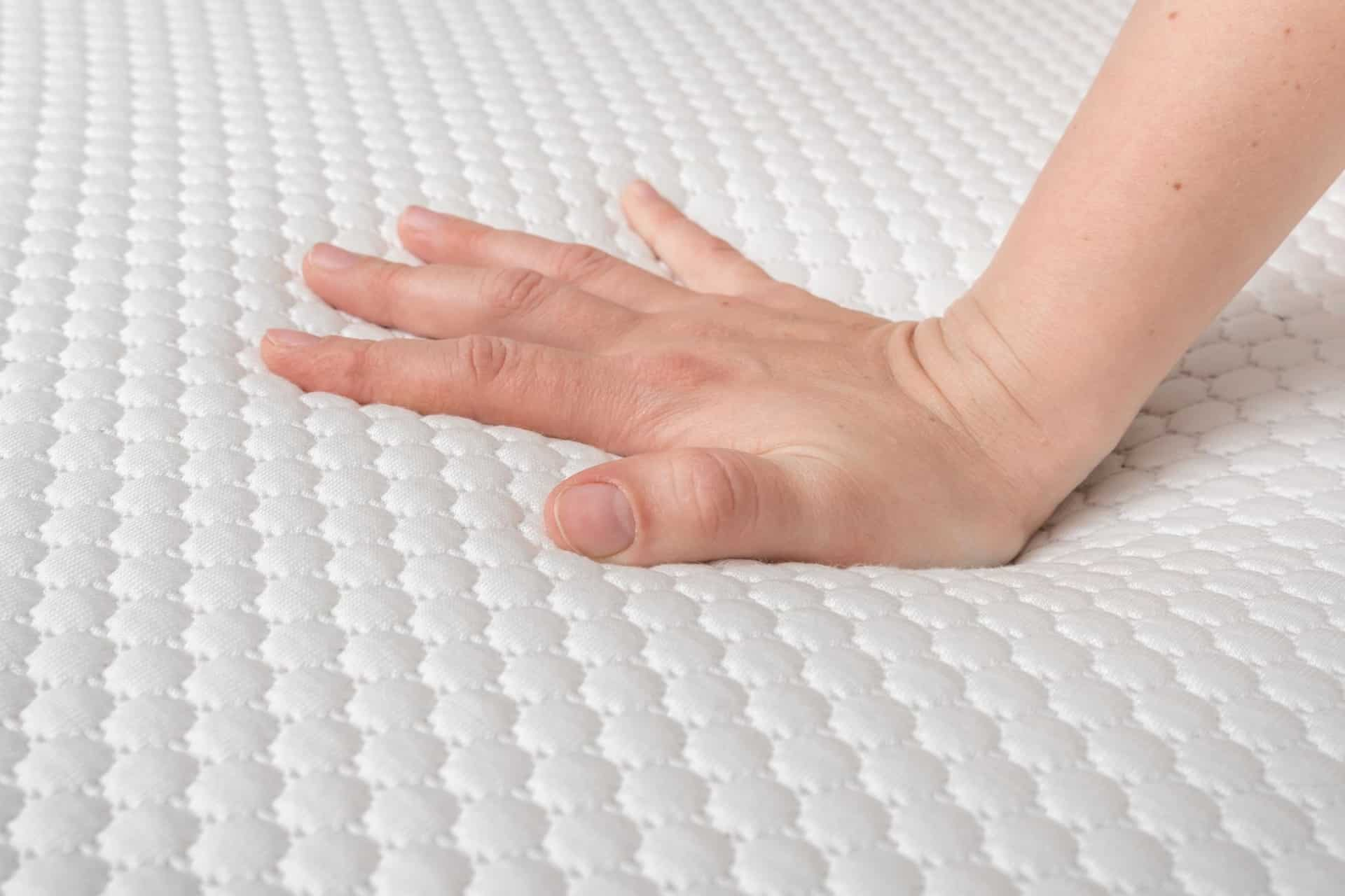 Hand of a woman testing a mattress.