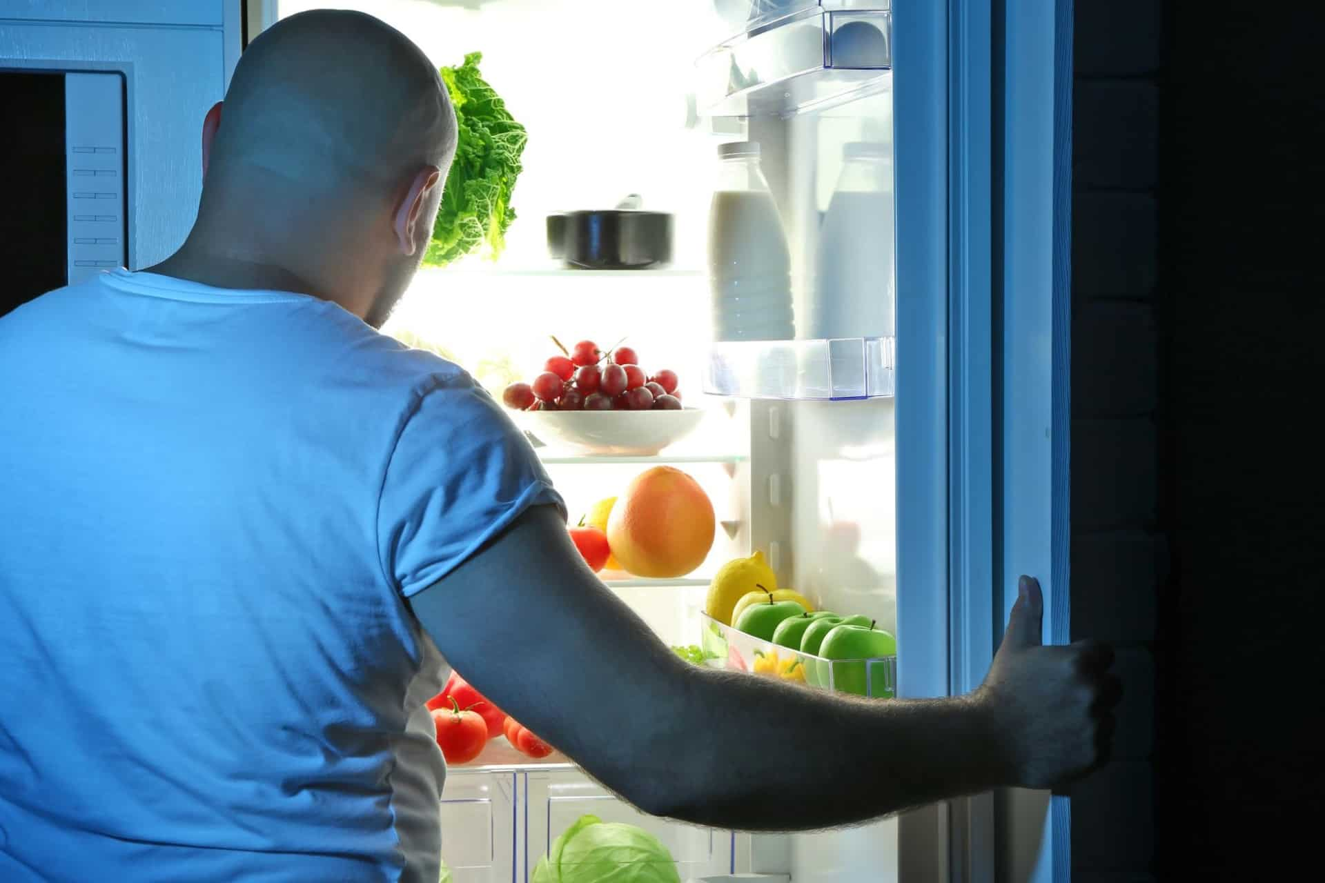 Man stands in front of refrigerator trying to decide what to eat before bed.