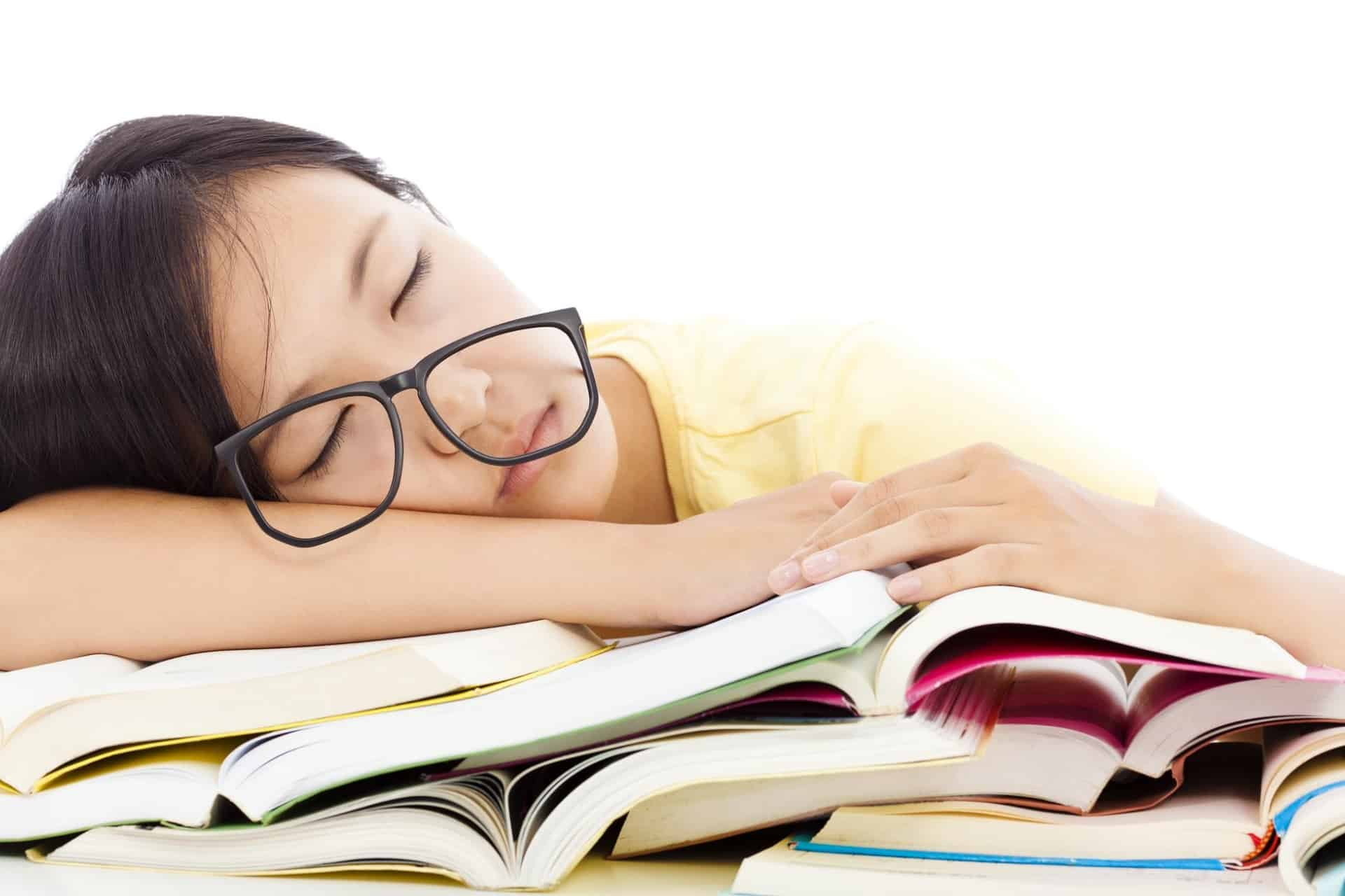 A tired student asleep on top of homework books.