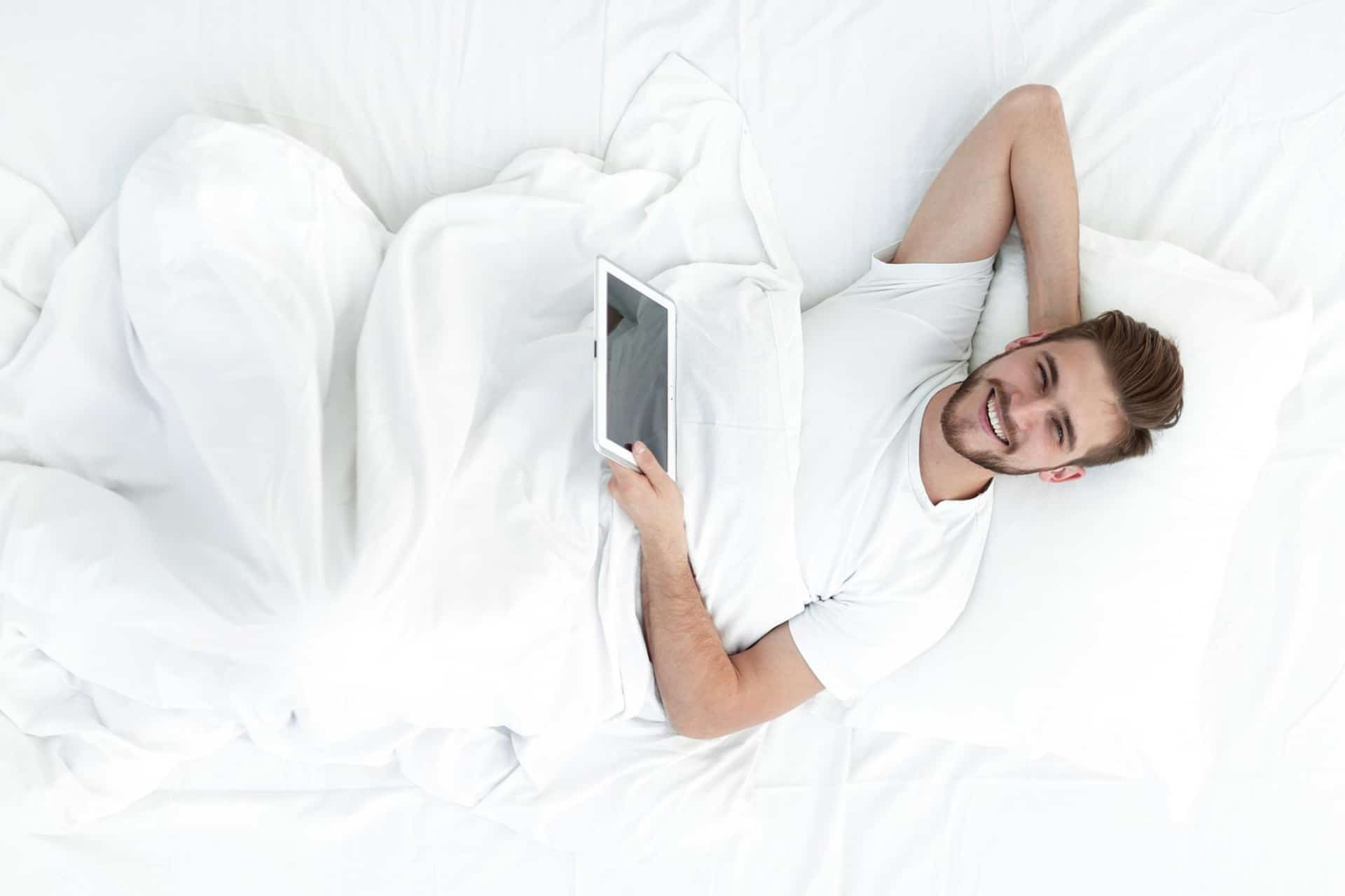 A man relaxes in bed with a tablet.