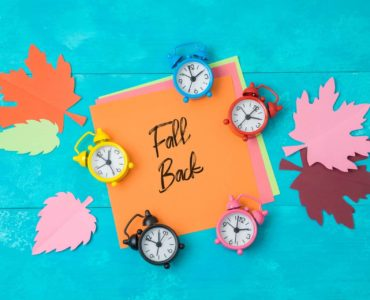 clocks and autumn leaves around a sign that says fall back