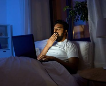 a man yawns while watching videos on a laptop in bed late at night