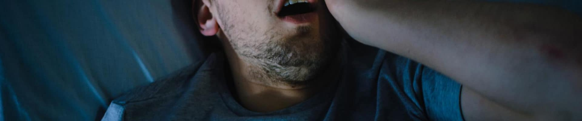 A man lies awake and scared to go to sleep.