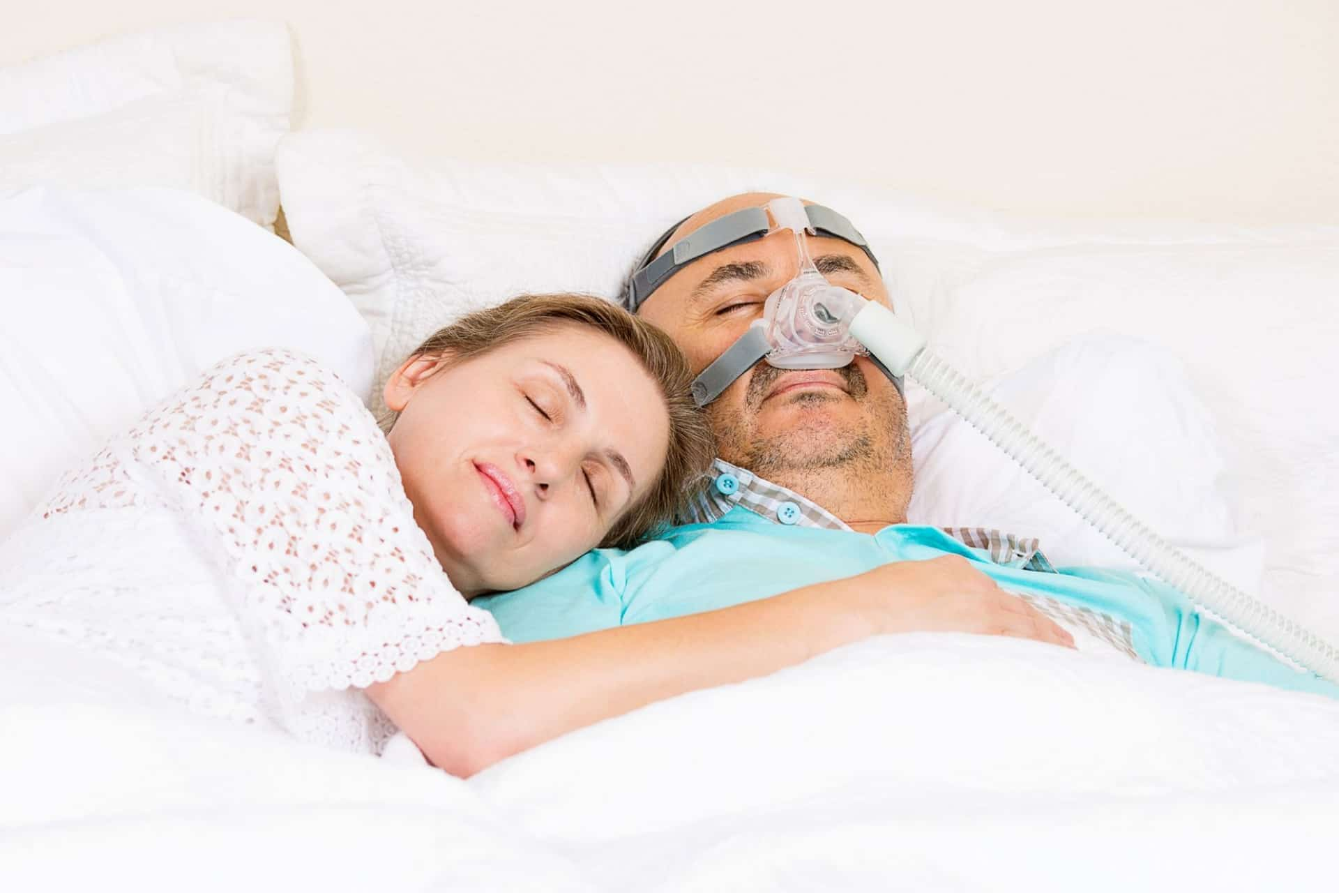 A couple sleeps in bed and the man is wearing a CPAP mask.
