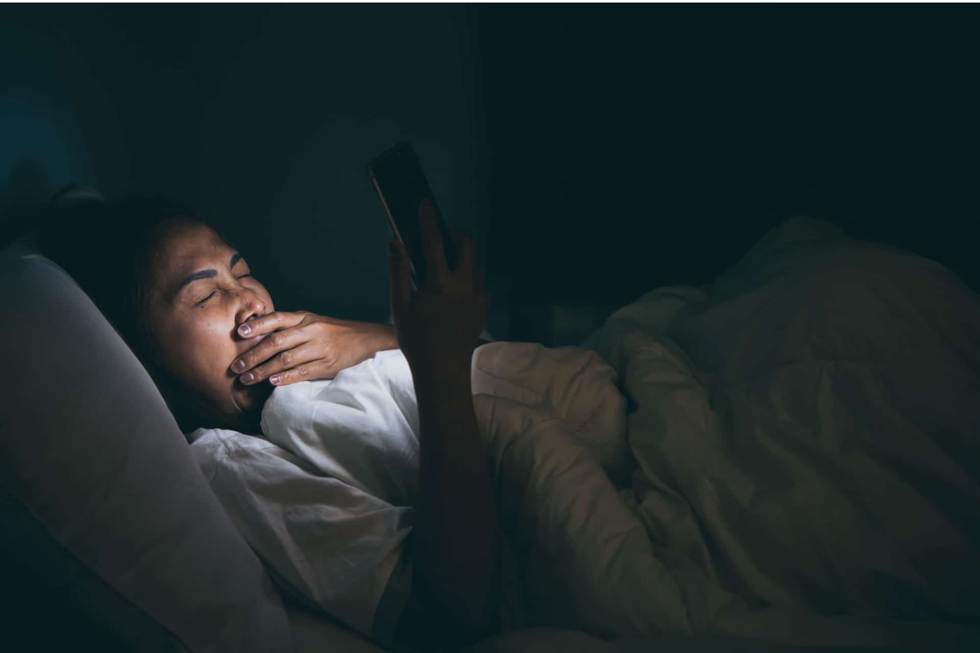 A woman yawns while looking at a mobile phone and trying to fall asleep.